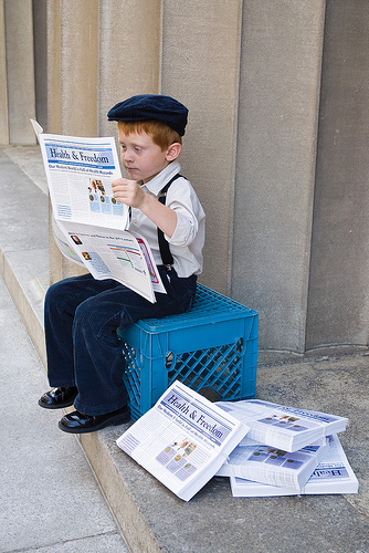Little boy in a cap reading newspapers